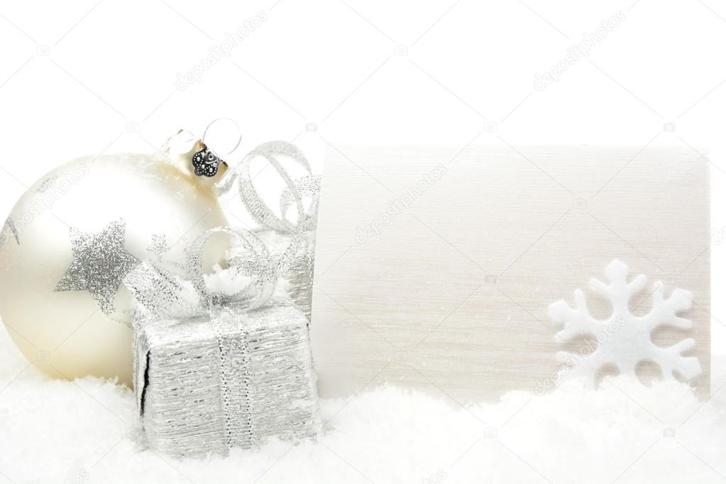 25be5c0993b3c Decoration of silver christmas baubles and gifts with wishes card on snow  white background — Photo by ...