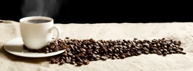 Panoramic view of frothy coffee cup with beans on fabric flax