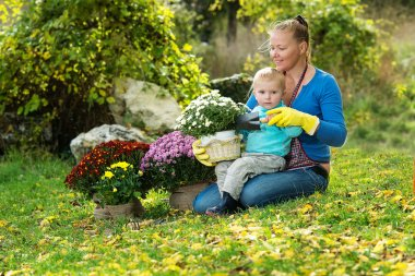 Young woman with a child are planting flowers