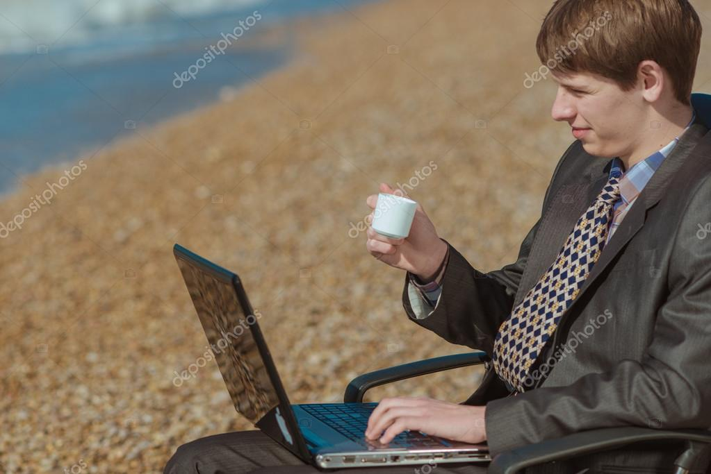 young businessman with a cup of coffee in an office chair on the