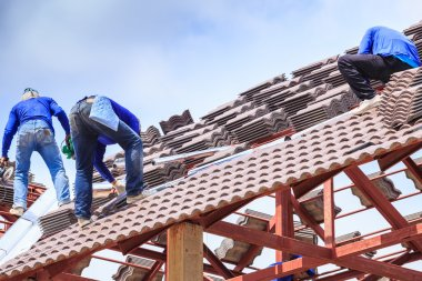 Workers install roof tile for house