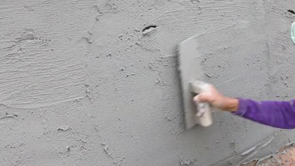 omítání betonu na zdi domu stavební dělník