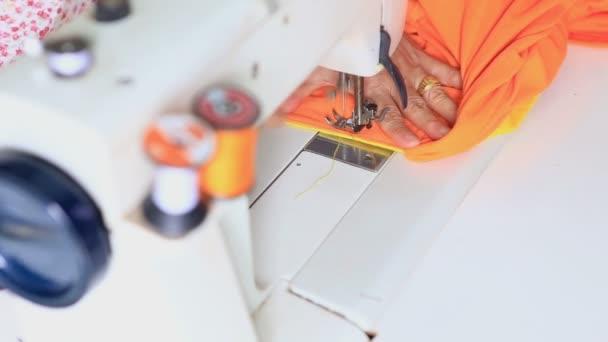 pracovník kontroly šicí stroj v továrně