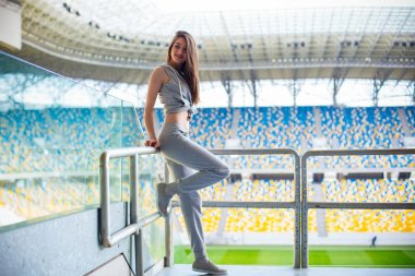 European Young brunette curly teen model creates a concrete stadium stairs, wearing sweat pants, sneakers