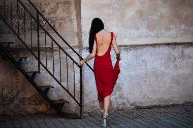Portrait of a beautiful woman in a red dress with a bare back. She climbs the stairs. Studio interior of the old palace.