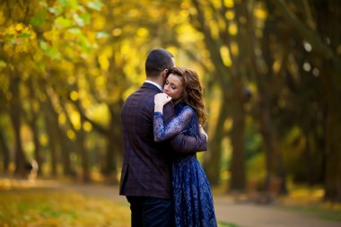 happy young couple embrace in a park in autumn