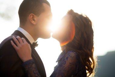 Couple kissing at sunset. wedding day, closed eyes