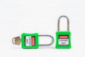 Zelený zámek kláves a štítek pro odříznutí procesu elektrický, přepínač číslo tagů pro elektrické odhlášení tag out na bílém pozadí