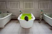 Žena ve vaně zelenou vodou