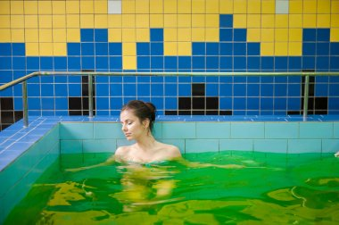 Woman in a pool with green water