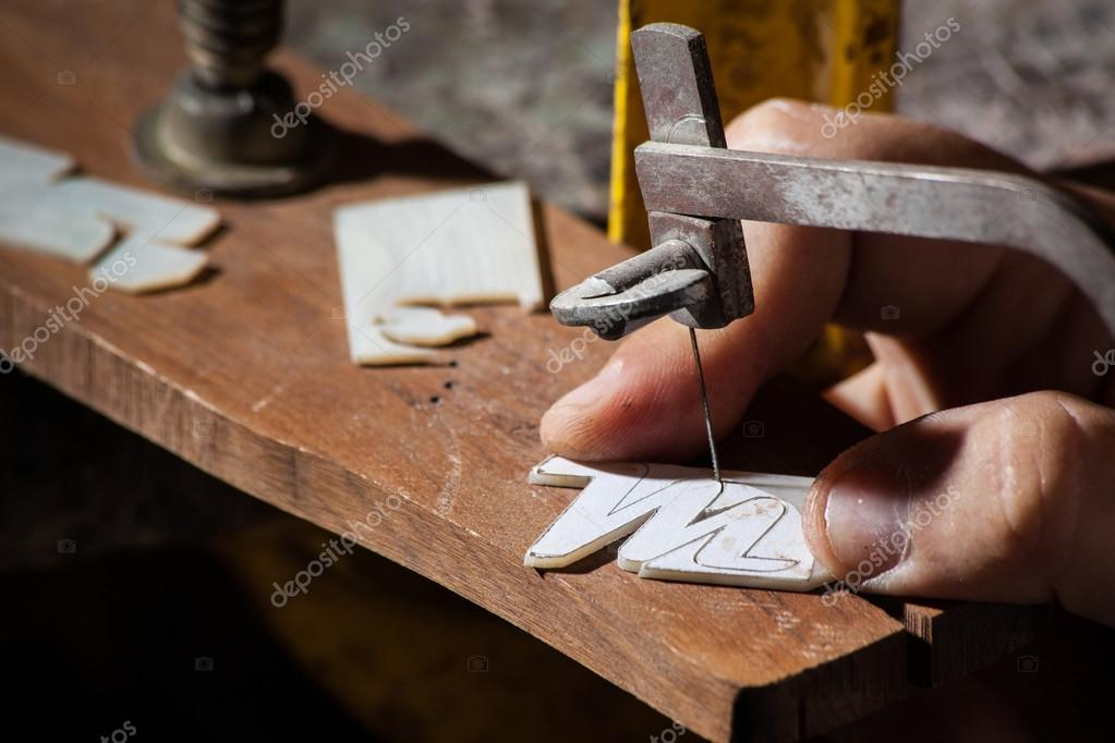 Luthier cutting a M letter mop inlay