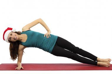 Christmas yoga woman in side plank pose