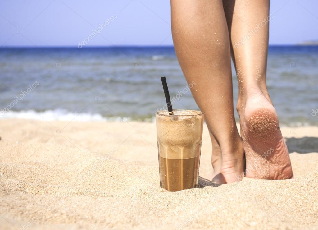 Iced coffee and female legs on a sandy beach