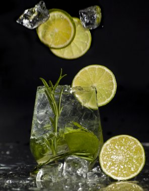 Gin and tonic cocktail with lime over black background.