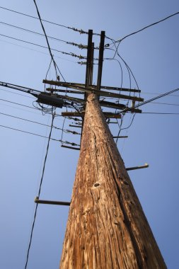 Wooden electricity pylon with blue sky