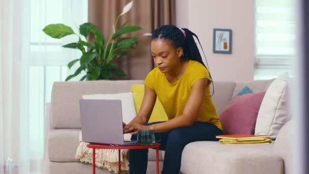 Freiberuflerin schwarze junge Geschäftsfrau arbeitet von zu Hause aus mit Laptop für die Arbeit Verwaltung von Online-Business-Deals Sperming entfernten Projekt sitzen im Wohnzimmer.