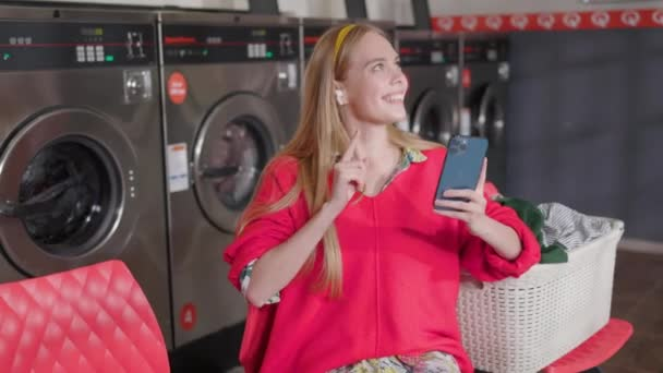 Schöne junge blonde Frau benutzt Telefon und Kopfhörer und hört Musik, während sie in der Waschküche Wäsche wäscht. Hausarbeit-Service Waschmaschine Trockner drinnen. Aus nächster Nähe. Zeitlupe