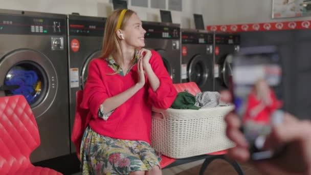 Hände halten Handy-Foto auf Hintergrund blonde Frau hört Musik Posen vor der Kamera sitzt in der Waschküche. Hausarbeit-Service Waschmaschine Trockner drinnen. Aus nächster Nähe. Zeitlupe