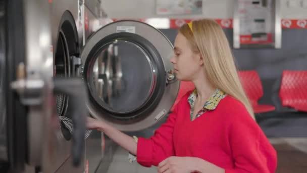 Glückliche Frau legt die Wäsche aus dem Korb in der Waschküche in die Waschmaschine. Hausfrau Hausarbeit Waschmaschine Routine drinnen. Zeitlupe