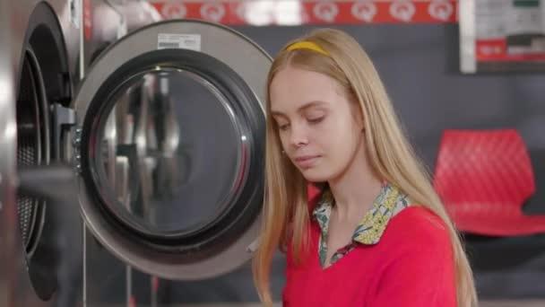 Portrait junge blonde Frau legt die Wäsche in die Waschmaschine aus dem Korb in der Waschküche. Hausfrau Hausarbeit Waschmaschine Routine drinnen. Zeitlupe