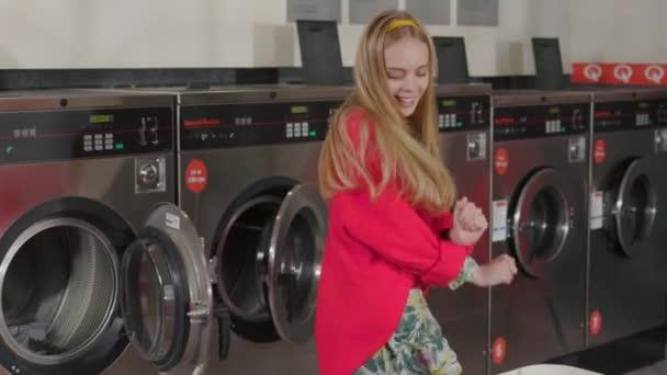 Lustige junge blonde Frau tanzt die Wäsche aus dem Korb in der Waschküche in die Waschmaschine. Hausfrau Hausarbeit Waschmaschine Routine drinnen. Zeitlupe