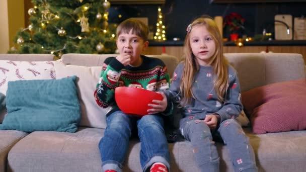Két csodálatos testvér gyerekei tévéznek rajzfilmeket és karácsonyi filmeket, popcornt esznek, aláírják a dalokat, és jól érzik magukat otthon. Családi fogalom.