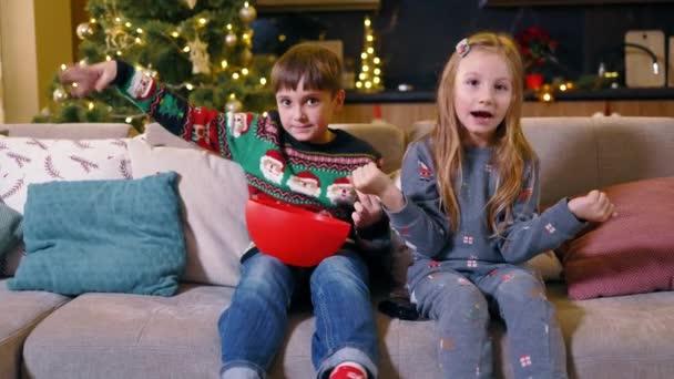 Szenteste. Két imádnivaló aranyos gyerek TV-t néz a nappaliban, popcornt esznek, és együtt játszanak a díszített karácsonyfa mellett. Téli ünnepek.