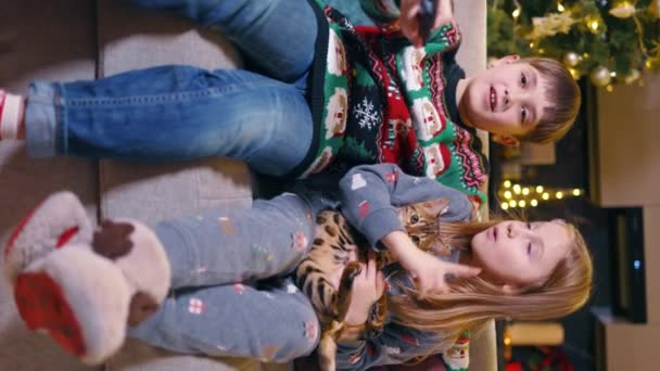 Zwei wunderschöne kaukasische kleine Kinder, die mit einer bengalen Katze spielen und niedliches Haustier streicheln, haben während der Winterferien gemeinsam Spaß. Weihnachtsfamilie. Geschwister. Kindheit. Vertikaler Schuss.