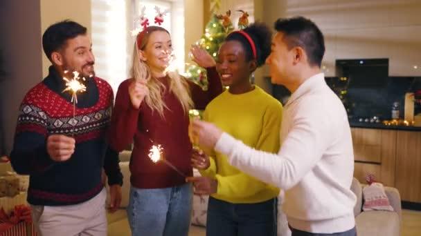 Egy csapat multiracionális barát, akik karácsonyi szerepet töltenek be égő csillagszórókkal, belenéz a kamerába az otthoni táncban. Hagyományos ünnep. Ünneplés. Boldog karácsonyt! Téli idő. Lassú mozgás.