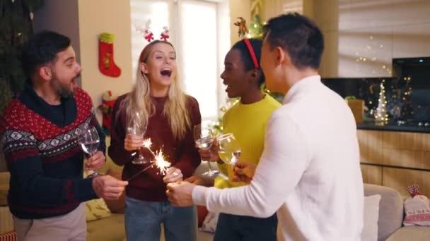 Fiatal, multiracionális barátokról, akiknek karácsonyi részük van, égő csillagszórókat tartva, bort iszogatva és mosolyogva néztek otthon a kamerába. Hagyományos ünnep. Ünneplés. Boldog karácsonyt! Téli idő