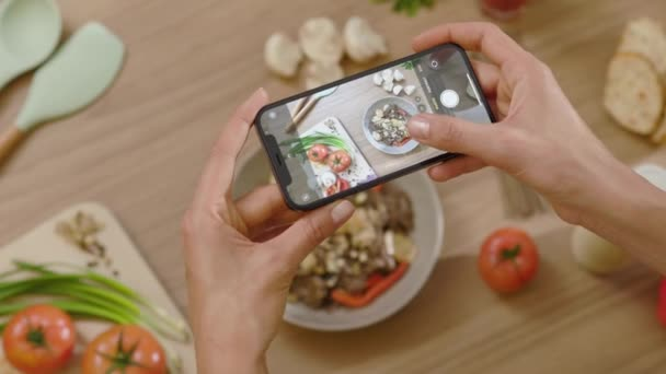 Hands woman taking a picture of tasty dish around board with vegetables on wooden table. Top view food photo. Blogging lunch blogger. Slow motion
