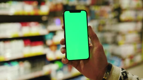 Close up man hand use mobile smartphone with vertical green screen in evening light supermarket blurred background. Mockup tapping display chromakey telephone. Slow motion