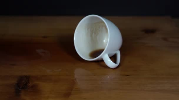 Camera moves to the tilt cup of coffee on wet wooden table with black background. Moving shot against object.