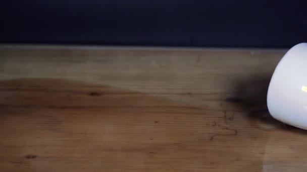Csobbanó csésze kávé fa asztal fekete háttér.