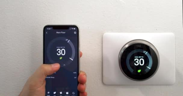 Calgary, Alberta, Kanada. 29. August 2020. Eine Person, die mit einem iPhone 11 Pro Max Energie spart, indem sie die Nest-App auf Celsiusmetriken nutzt, mit einem kabellosen Nest-Lernthermostat an einer weißen Wand.