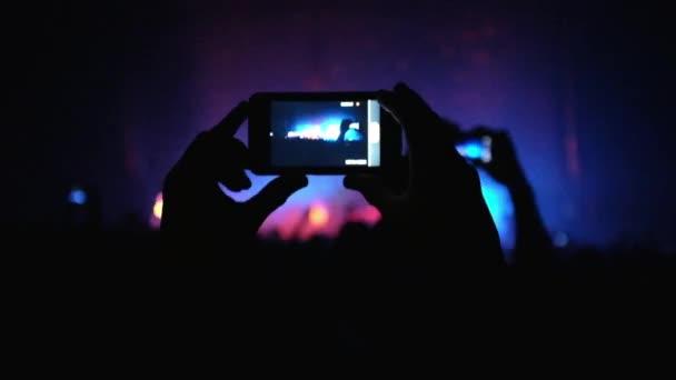 Fanoušci mává rukou a držte telefon s digitálním displeji