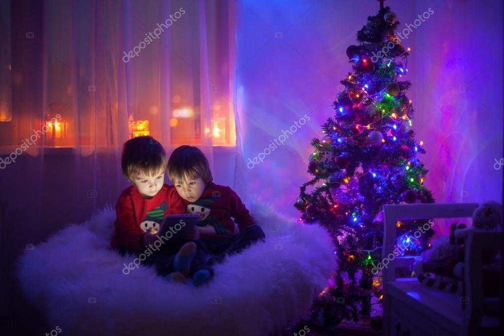 Dos muchachos jugando con la tablet en casa, junto al árbol de ...
