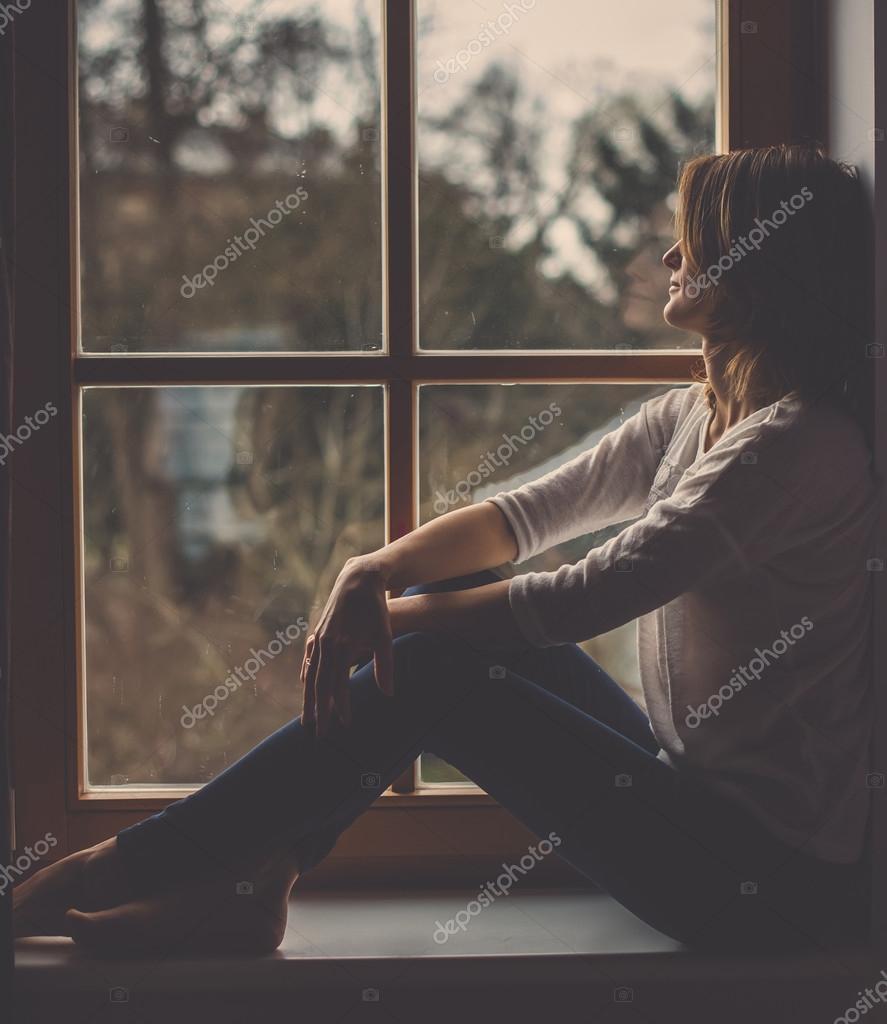 fd7297fe4 Jovem mulher atraente, sentado na janela, olhando lá fora — Fotografia de  Stock
