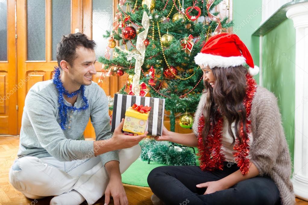 Paare, die im Sankt-Hut mit Weihnachten und Neujahr Geschenk ...