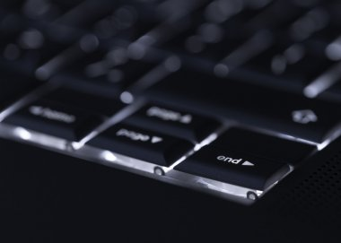 Closeup of backlit computer laptop keyboard selective focus on e