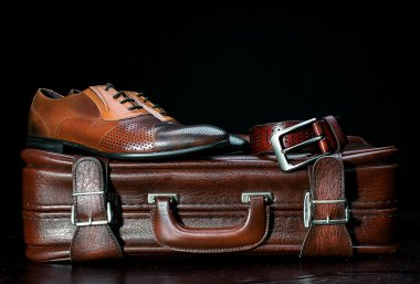 men's leather shoes and a suitcase