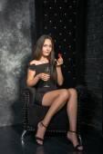Fotografie Frau in einem schwarzen Kleid sitzt in einem Hochstuhl mit Erdbeere