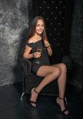 Fotografie Frau in einem schwarzen Kleid sitzt in einem Hochstuhl mit Erdbeere eine