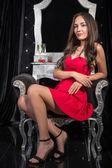 Fotografie Frau in einem roten Kleid sitzt auf einem Stuhl vor Registerkarte Dressing