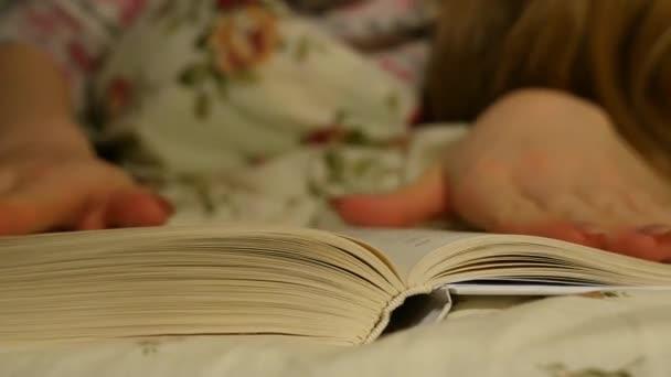 Mladá dívka čtení knihy před ulehnutím ke spánku
