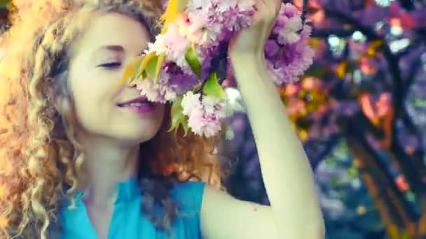 Mladá žena voní kvetoucí třešeň