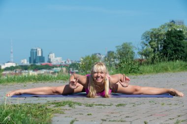Young woman practicing yoga in park at sunny day