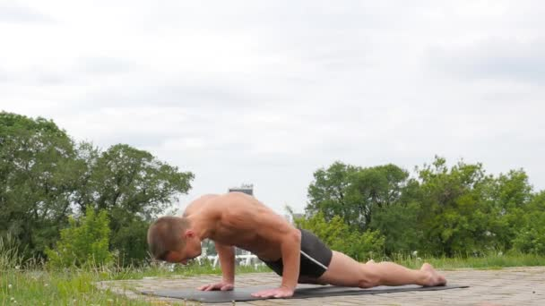 Handsome Flexible Athletic Man Doing Yoga Asanas In The Park