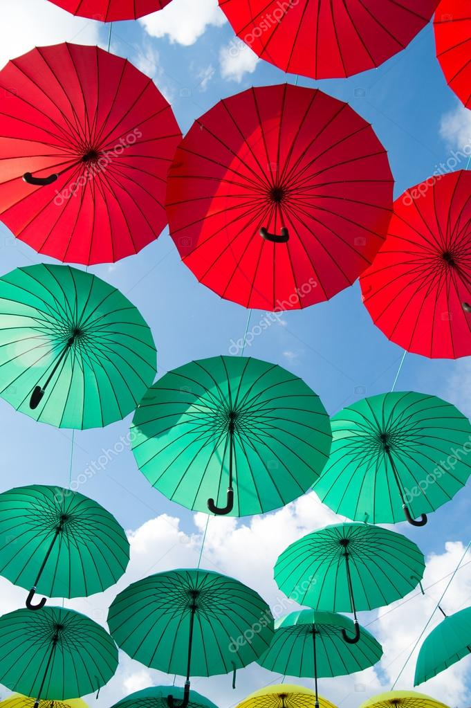 25d34d31b Bright colorful red and green umbrellas background against cloudy sky at  sunny day — Photo by stetsik