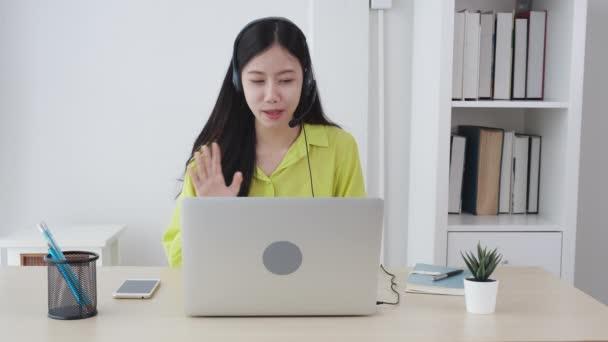 Mladé asijské obchodní žena pomocí notebooku pro videokonference on-line se sociální distancování, podnikatelka pracuje s videohovory, nové normální, komunikace a práce z domova koncept.
